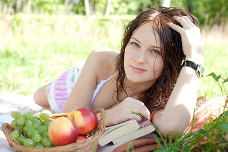 Attractive woman lying on the grass with book and fruits photo