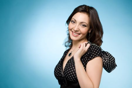 Portrait of a happy Jewish woman with a grin in retro black dress. She holds a small black dolly-bag. Over blue background Stock Photo - 6637121