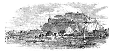 Petrovaradin Fortress in Novi Sad, Serbia, during the 1890s, vintage engraving. Old engraved illustration of Petrovaradin Fortress with river and boats in front.