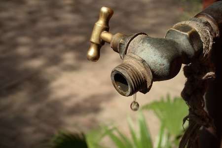Image of a drop of water falling from an old metal conduct. The last drop of water