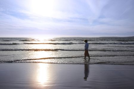 a lady walking in the warm sea photo
