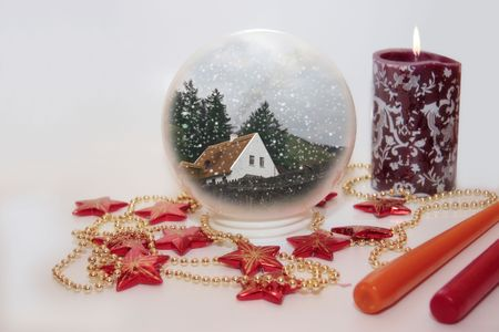 aglow: christmas crystal ball against a bright background with candles Stock Photo