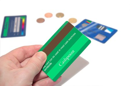 bankcard: a man holding a credit card (made up fake card ) with more fake cards and coins in the background