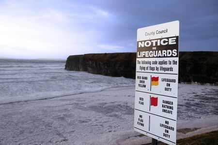 a warning notice on a ballybunion beach in ireland about when lifeguards are on duty photo