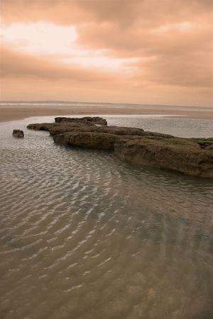 mud banks on the west coast of ireland near ballybunion under a red sky photo