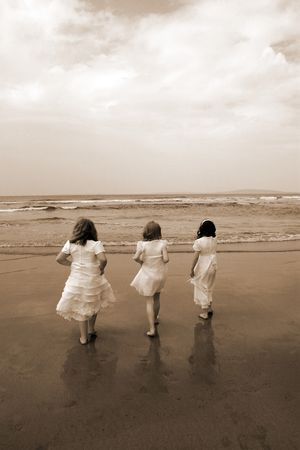 a picture of the time of the first communion and the joy thereafter of three friends going into the sea for a paddle photo