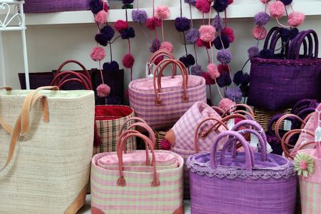 straw bags of various colors in a market