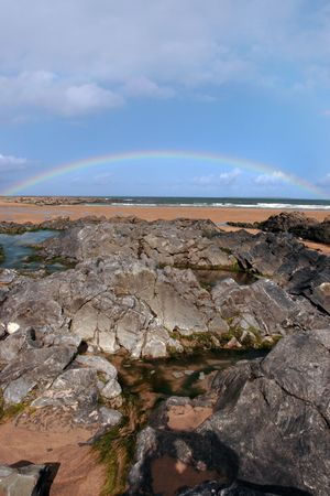 a rocky beach on a warm wet day with a calm sea and a rainbow after a shower an ideal place to have a walk in ireland photo