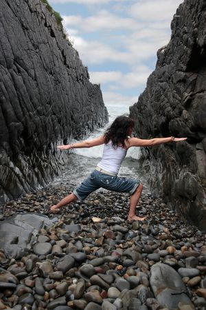 a beautiful woman practicing her yoga on the rocks in a ravine as the waves roll in