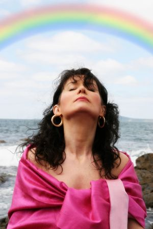 a beautiful woman meditating on the rocks showing a healthy way to live a happy and relaxed lifestyle in a world full of stress with a beautiful rainbow in the background Stock Photo - 3390113