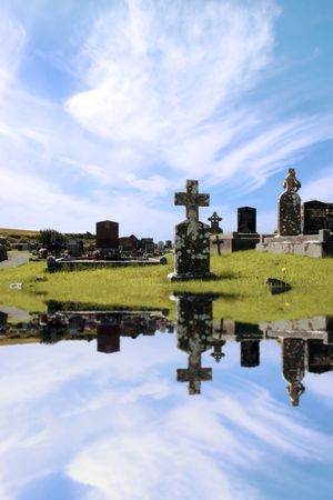 an old irish graveyard in Kerry on the west coast of Ireland reflected in water