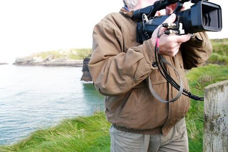 a cameraman filming on the cliff edge in ballybunion ireland Stock Photo