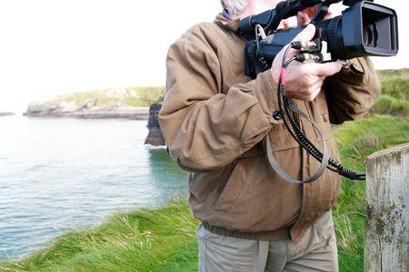 film crew: a cameraman filming on the cliff edge in ballybunion ireland Stock Photo