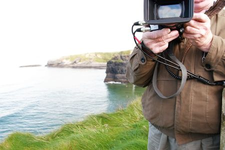 a cameraman filming on the cliff edge in ballybunion ireland photo