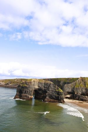 ballybunion: a canoeist at the virgin rock in ballybunion ireland as seen from the cliffs