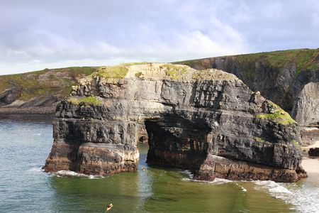 canoeist: a canoeist at the virgin rock in ballybunion ireland as seen from the cliffs