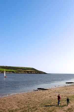 youghal: a father and son walking on the beach in youghal harbor ireland