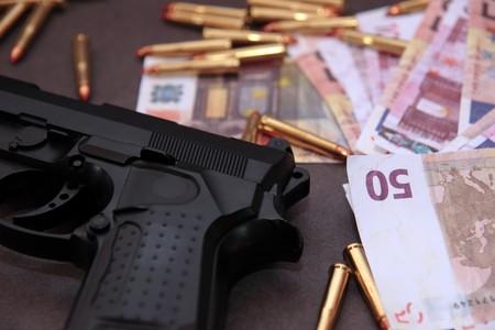 illicit: uno stash di droga e denaro pistola mostrando un costo pericolose per la vita contro un fondo scuro Archivio Fotografico