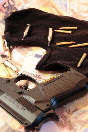 mugger: balaclava, money, gun and bullets showing concept of a robber or terrorist activity Stock Photo