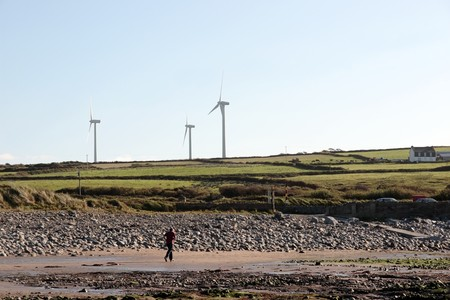 co  kerry: man running on beale beach co kerry ireland on a cold winters morning with turbines in the background