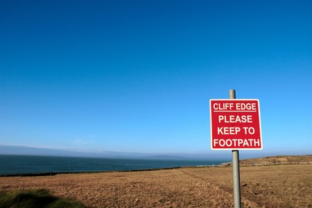 a warning sign of danger at the cliff edge photo