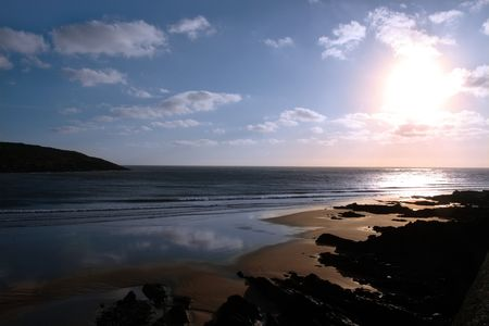 youghal: the waves with reflection crashing in on youghal beach ireland
