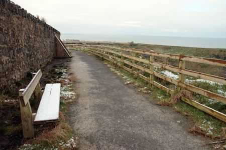 ballybunion: snow covered bench on the ballybunion cliffside walk in winter