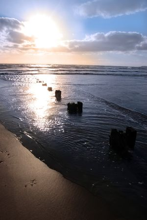 youghal: wave breakers at sunset on a beach in youghal county cork ireland