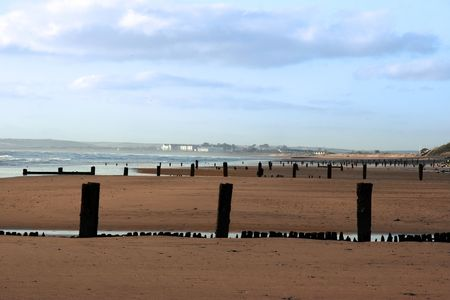youghal: wave breakers on a beach in youghal county cork ireland