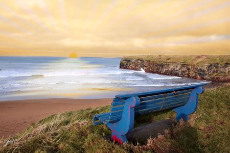 ballybunion bench in winter with view of beach and cliffs as the sun sets photo