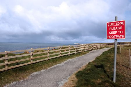 cliff edge: a warning sign of danger at the cliff edge walk