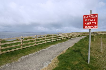 steep cliffs sign: a warning sign of danger on the cliff edge walk in ballybunion