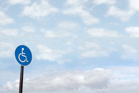 universal wheel chair sign with clouds in the background