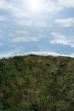 a white picket fence on top of a hill against a cloudy sky photo