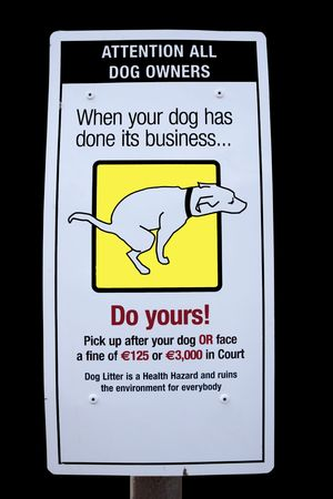 sign warning about fines for dogs fouling isolated on black photo