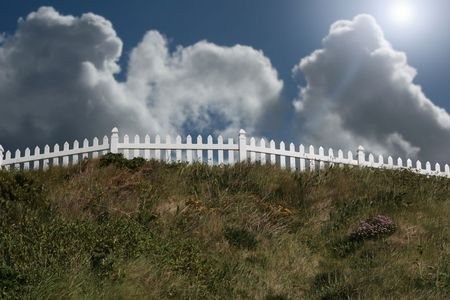 a white picket fence on top of a hill photo