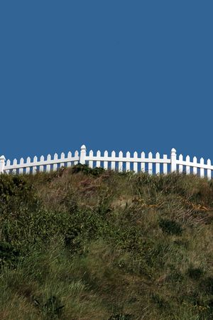 a white picket fence on top of a hill against a blue sky photo