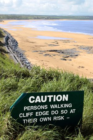 steep cliff sign: a caution sign on a cliff edge in ballybunion