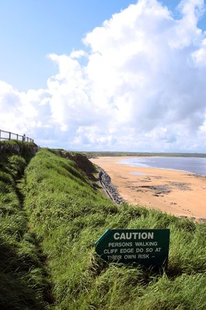 steep cliffs sign: a caution sign on a cliff edge in ballybunion