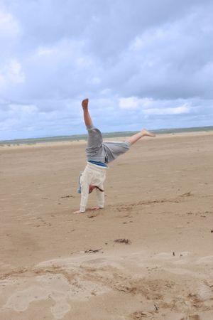 a young girl having fun doing a cartwheel on the beach photo