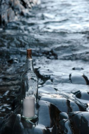 castaway: a bottle with a blank message standing on a rocky coastline