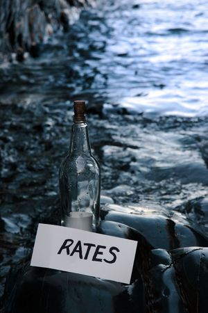 a bottle with a message on water rates standing on a rocky coastline photo