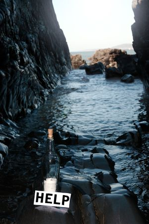 a bottle with a help message label standing on a rocky coastline photo