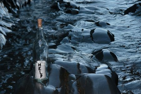 castaway: a bottle with a help message standing on a rocky coastline Stock Photo