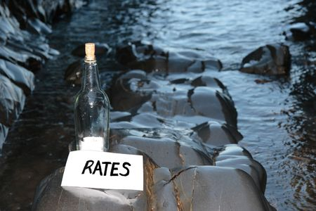 a bottle with a message on water rates standing on a rocky coastline Stock Photo - 5631760