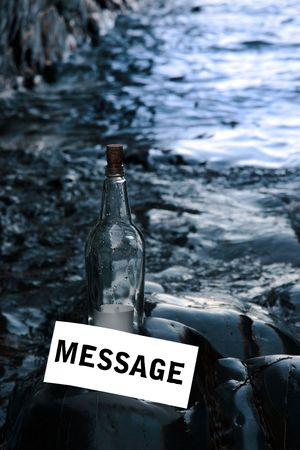 a bottle with a message standing on a rocky coastline photo