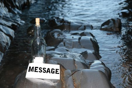a bottle with a  message standing on a rocky coastline Stock Photo - 5631738