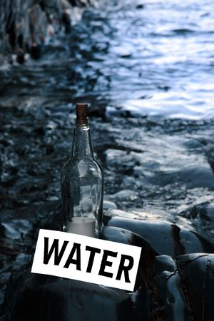 castaway: a bottle with a message on water standing on a rocky coastline Stock Photo