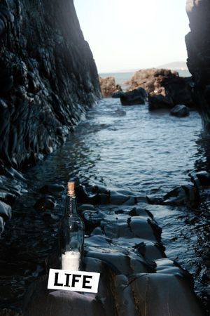 a bottle with a message on water is life standing on a rocky coastline photo