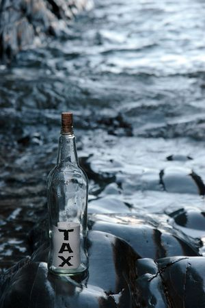 a bottle with a message on water taxes standing on a rocky coastline photo